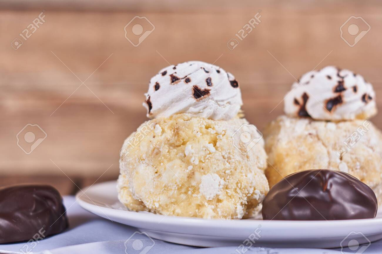 Two airy desserts with meringue in chocolate drops with prunes and butter cream and the chocolate zephyr in a white plate on a wooden background - 120054098