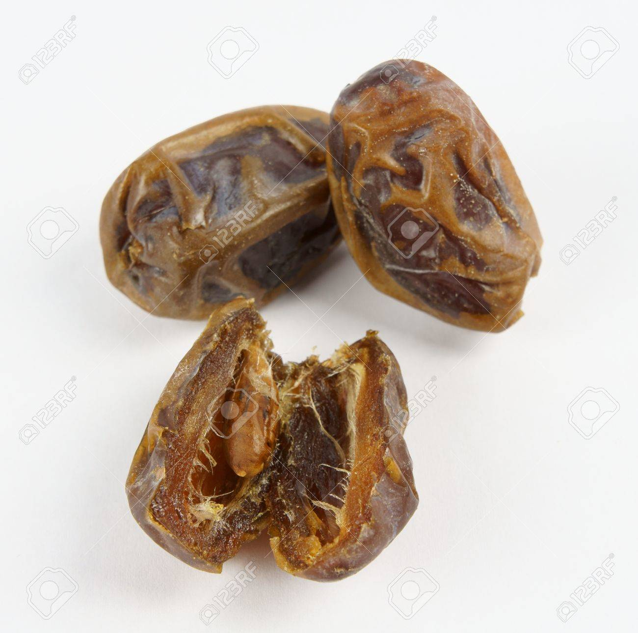 Medjoul date in focus cut up showing the seed in front of two whole fruits; on neutral white background. Stock Photo - 12826748