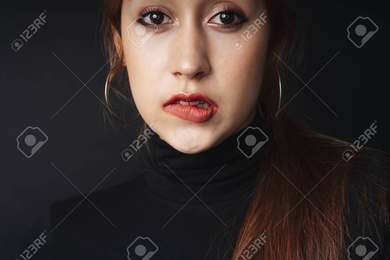 Close up portrait of pretty beautiful young woman wearing black sweater isolate over dark background. Woman using red lipstick. Cosmetic concept. Bitting lips posing. - 150103012