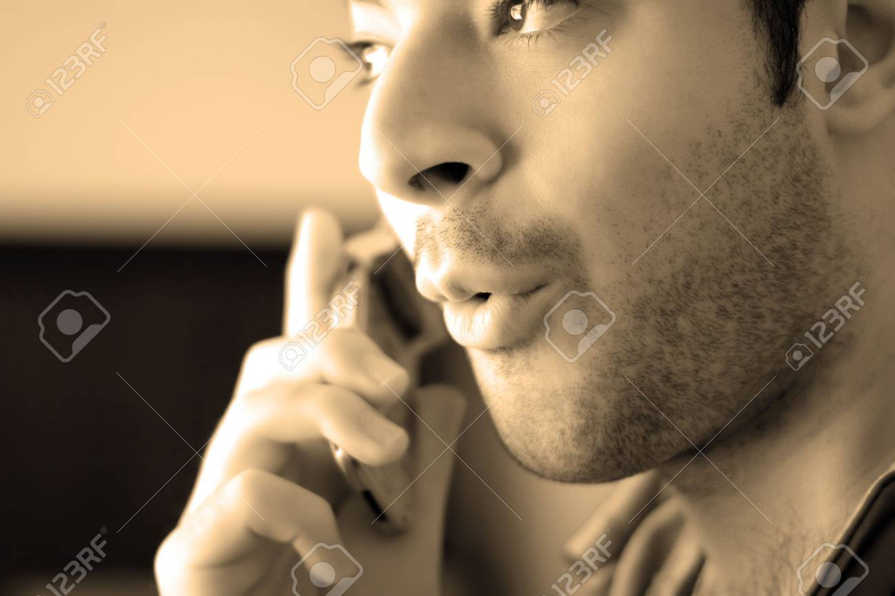 Sepia toned portrait of a young man on his celly phone - he looks surprised from what he has just heard. Stock Photo - 3018221