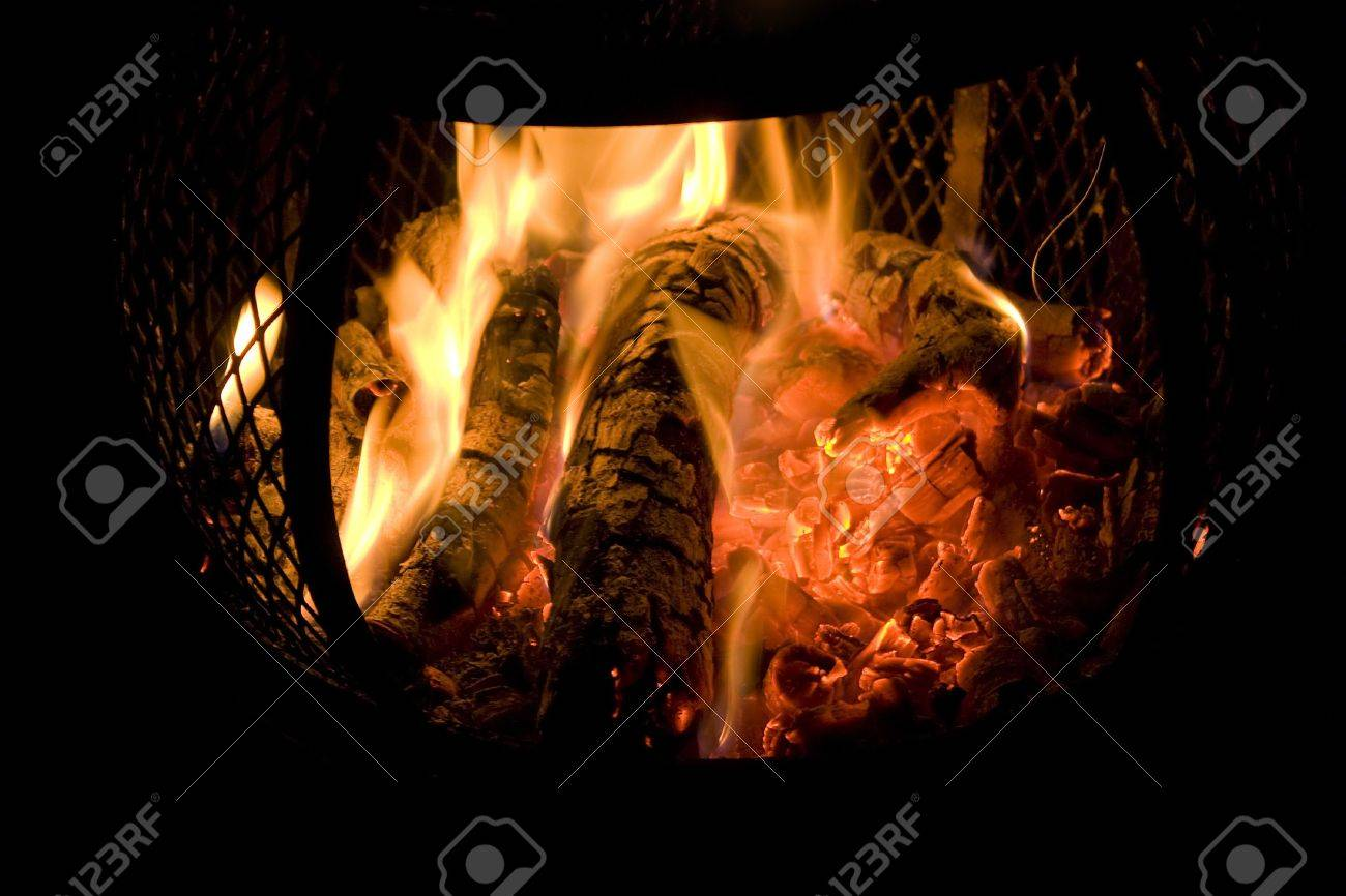 a red fire burning in a backyard chiminea with red glowing