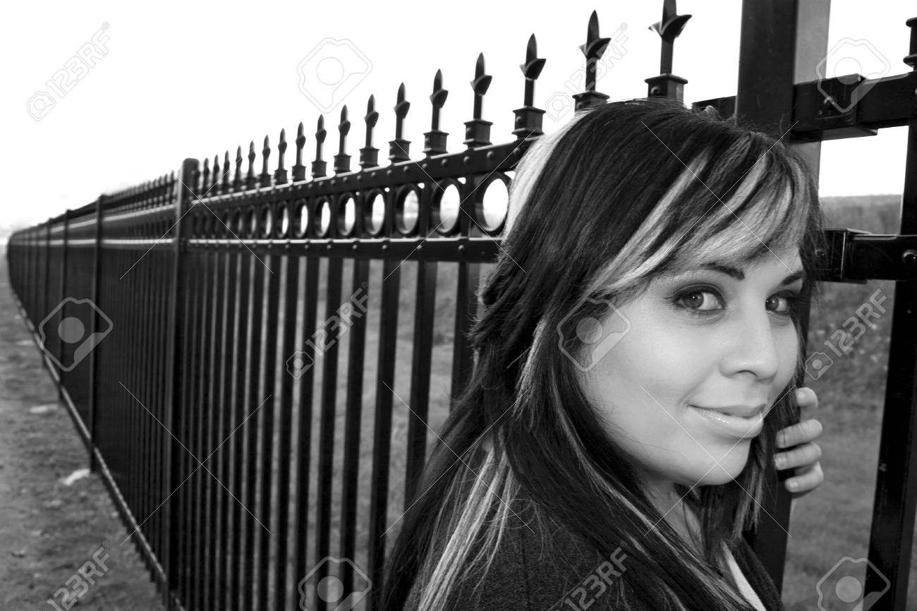 A Young Girl With Highlighted Hair Posing By A Fence Black Stock