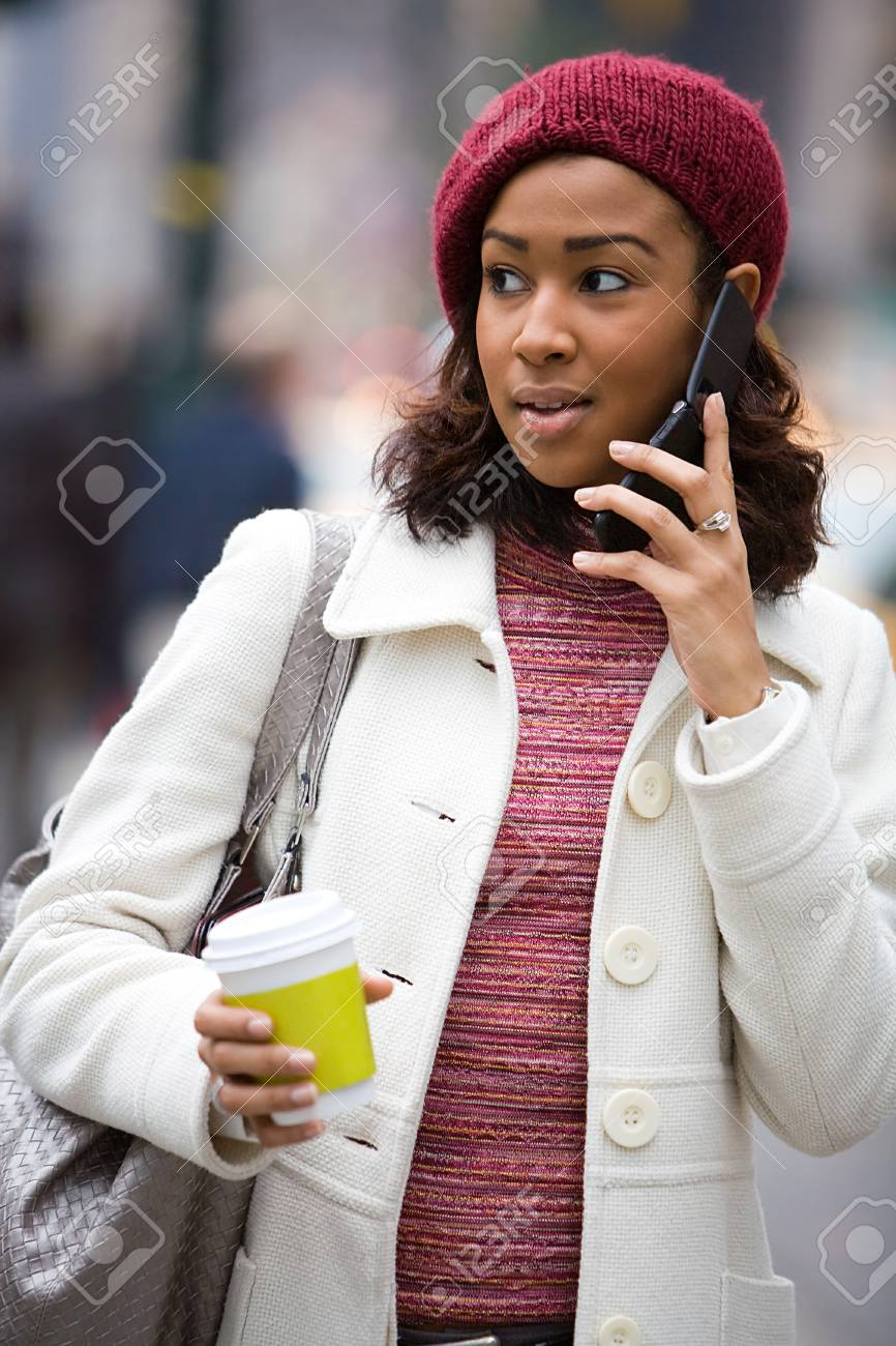 An attractive business woman talking on her cell phone along with a hot coffee. Stock Photo - 4288540