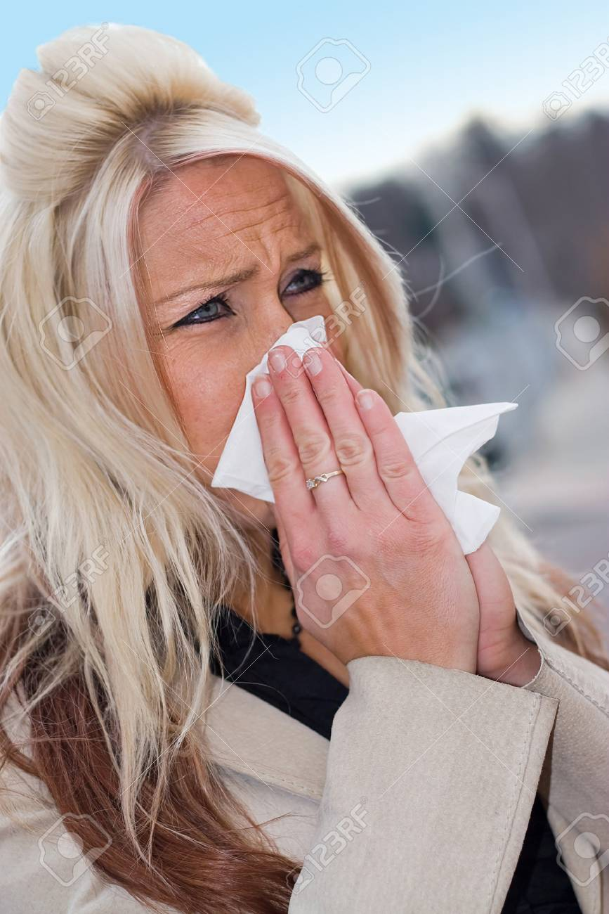 This young woman sneezing into a tissue either has a cold or really bad allergies. Stock Photo - 4324336