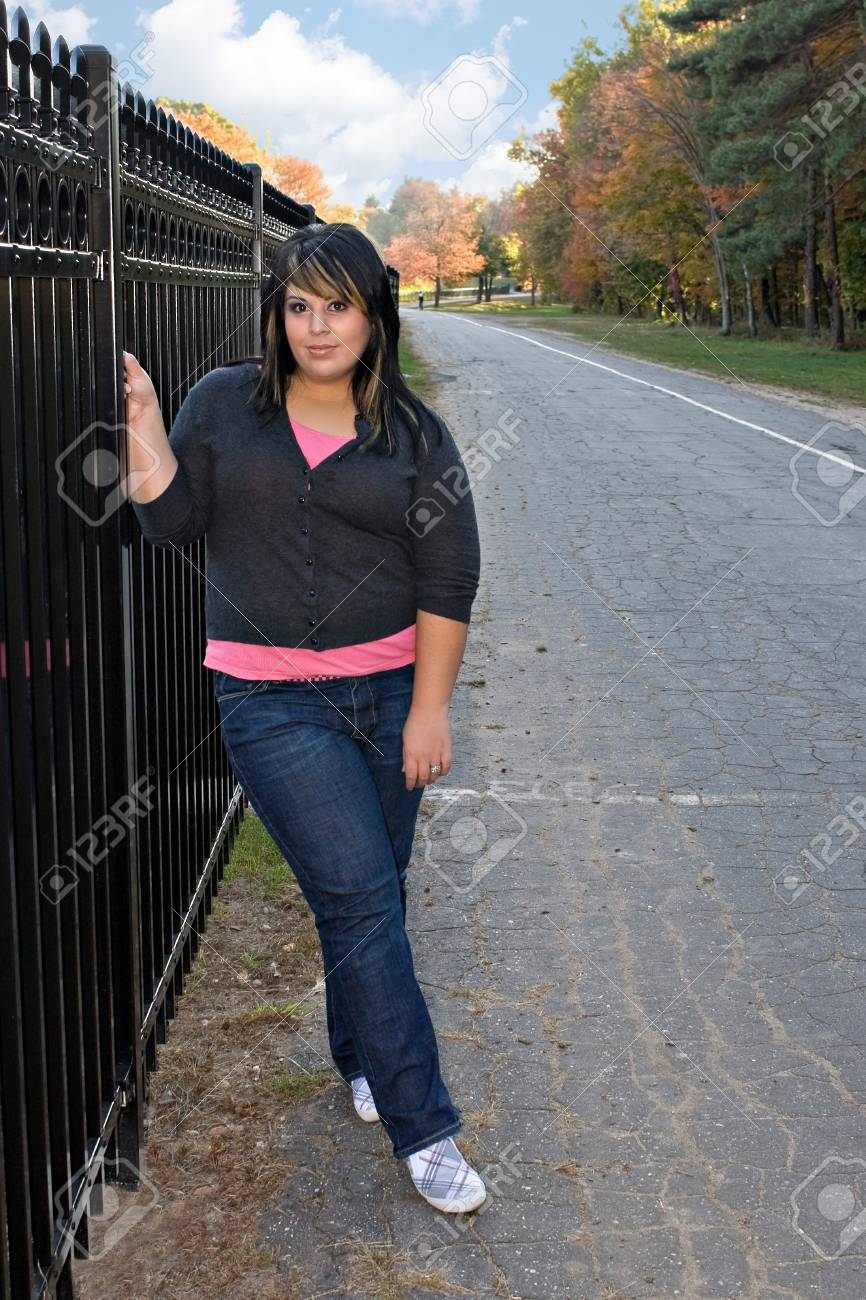 A young girl with highlighted hair posing by a fence on a nice autumn afternoon. Stock Photo - 4519301
