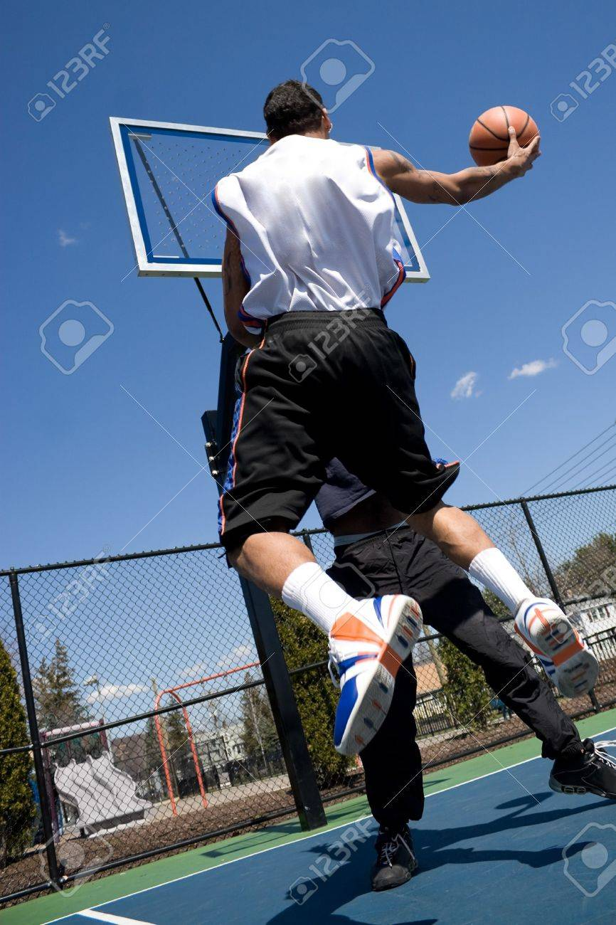 A young basketball player driving to the hoop with some fancy moves during a one on one game at the park. Stock Photo - 5094535