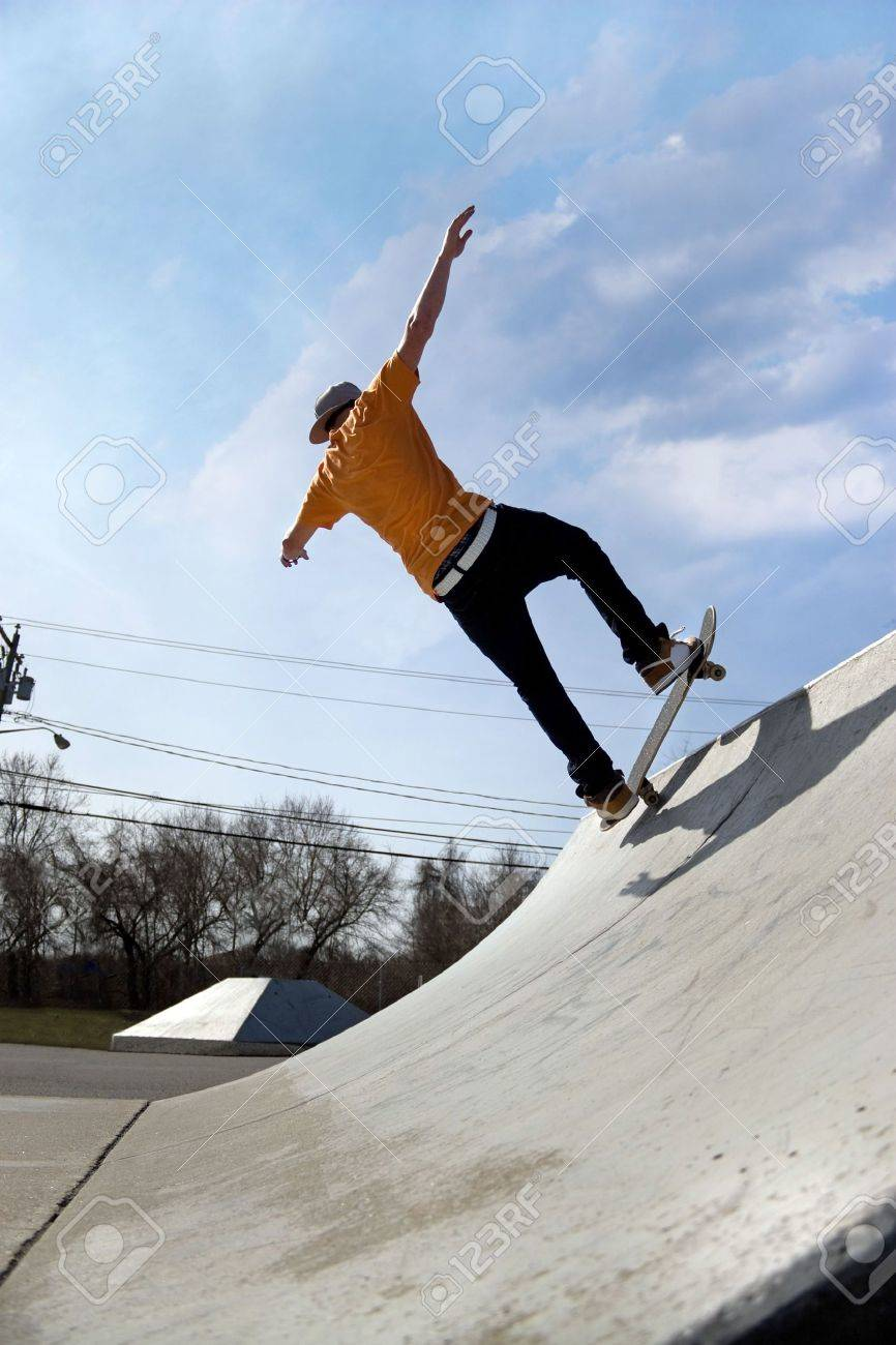 Skateboarding 5469352-Portrait-of-a-young-skateboarder-skating-down-a-ramp-at-the-skate-park--Stock-Photo