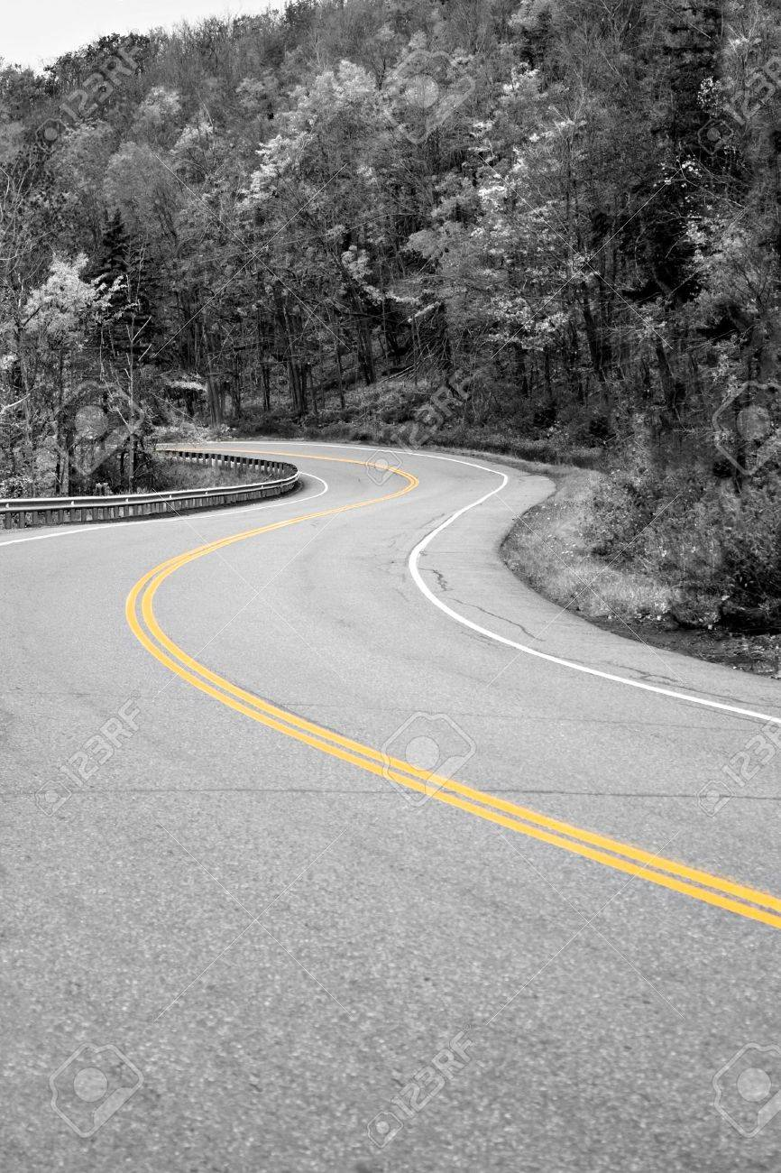 A curved New England road with selective isolated color and the center double lines in yellow. Stock Photo - 5765381