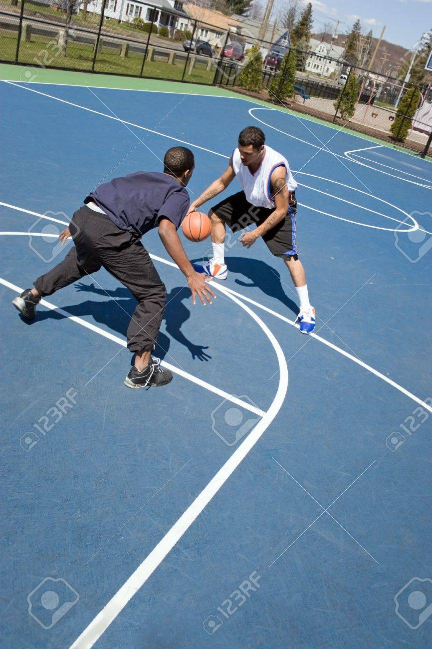 A young basketball player guarding his opponent during a one on one basketball game. Stock Photo - 5827026