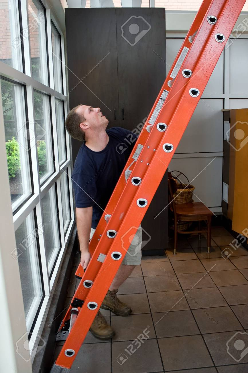 A young HVAC technician electrical worker or painter setting up a ladder to service something on the roof of the building. Stock Photo - 6048665