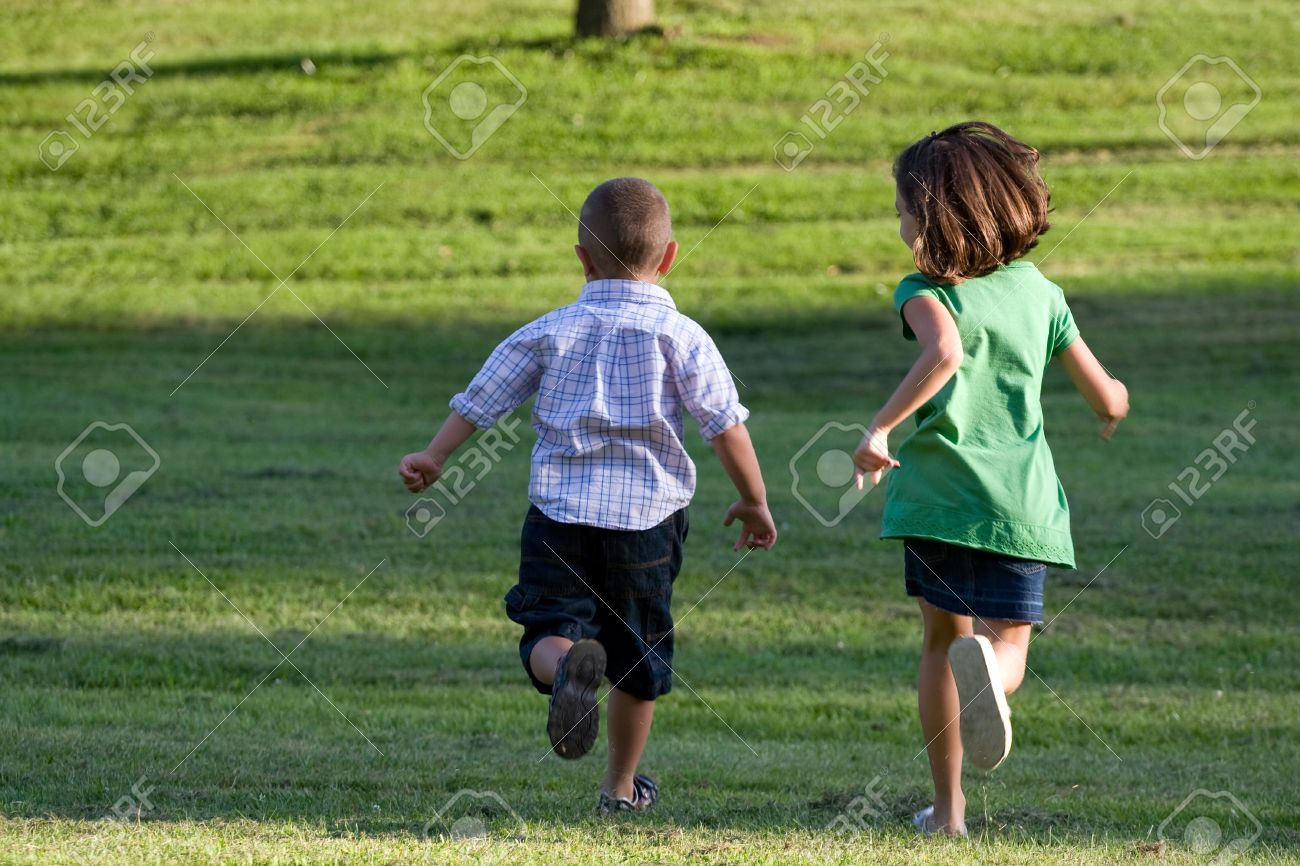 A little boy and girl run through the grassy field without a care in the world. Stock Photo - 6108087