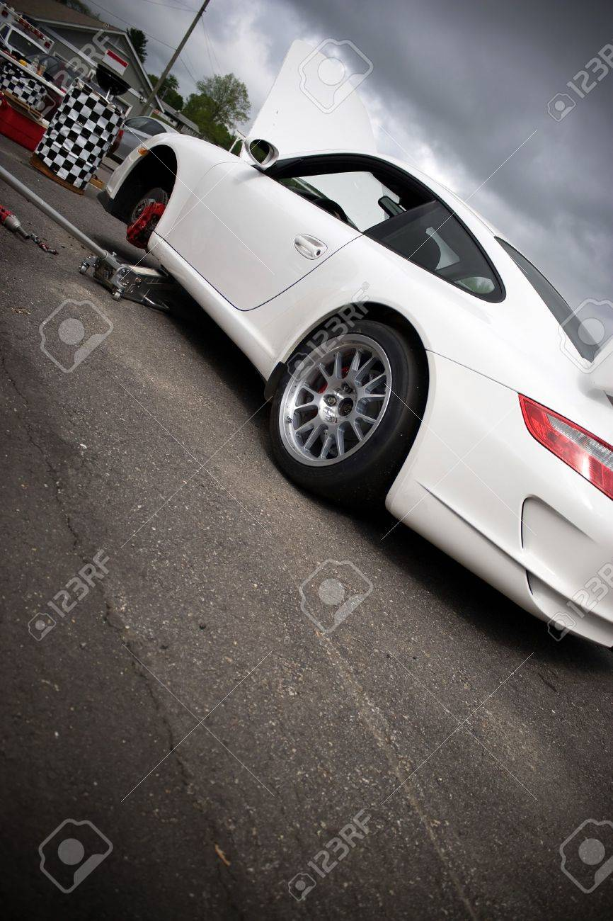 A sports car parked in the race track pit area is getting worked on.   Stock Photo - 6124470