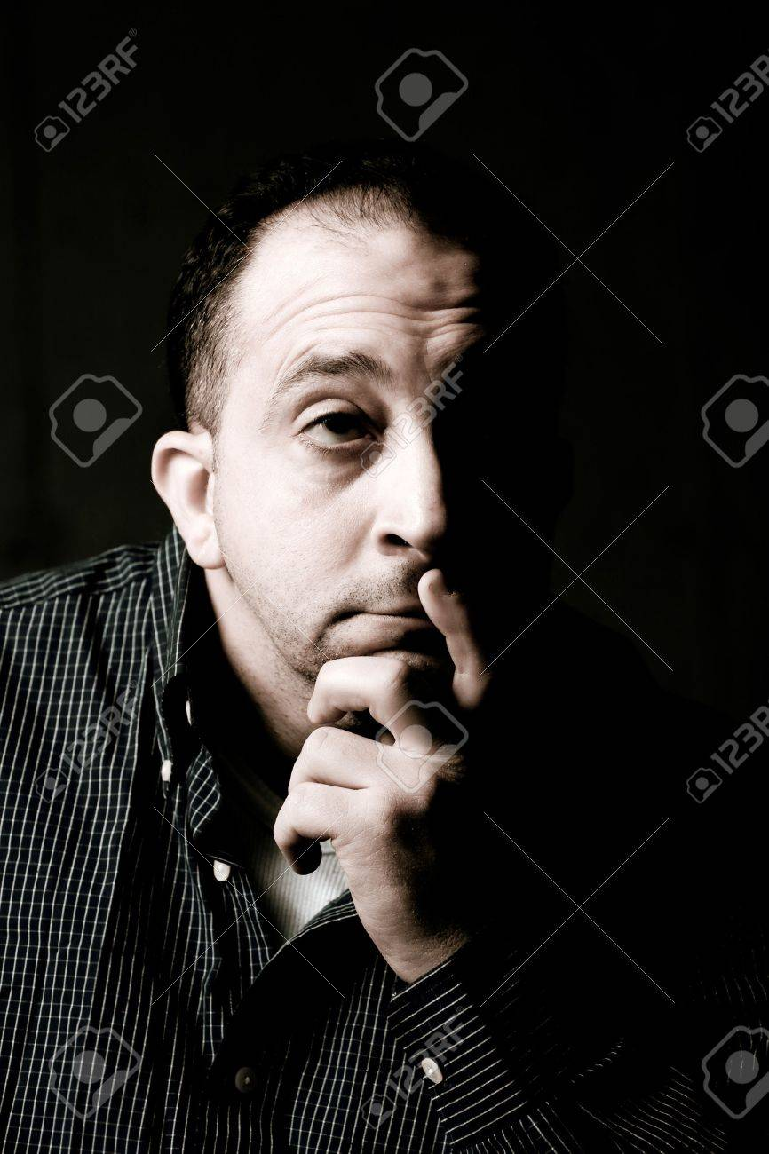 High contrast portrait of a middle aged man with a contemplative look on his face