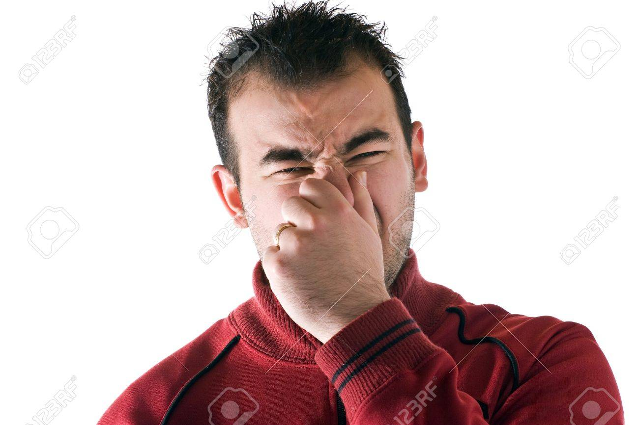 A young man holds or pinches his nose shut because of a stinky smell or odor. Stock Photo - 7054481