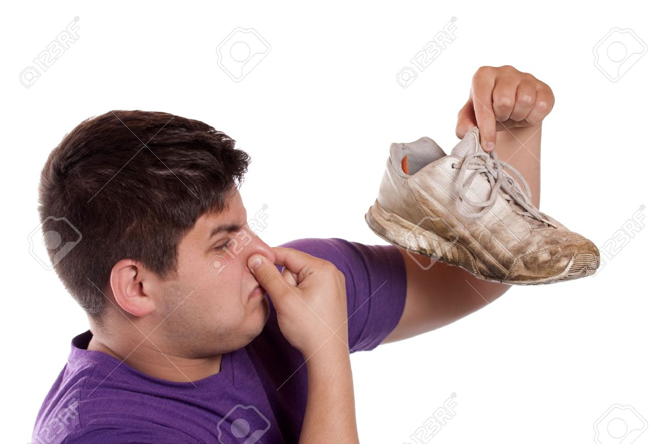 A teenager pinches his nostrils closed over the odor given off from the athletic shoe he is holding. Stock Photo - 7908051
