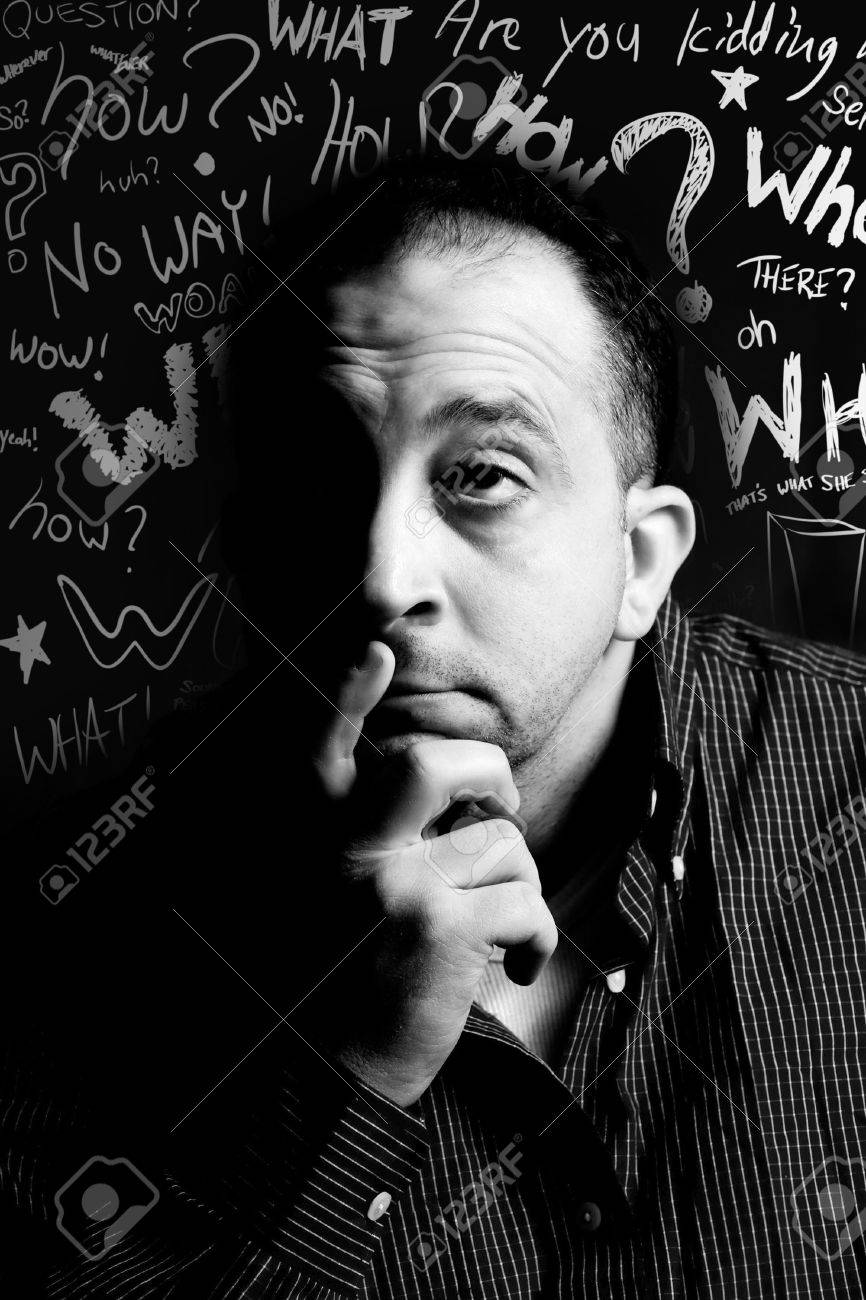 A middle aged man with his hand on his chin looks like he is thinking deeply about something. Doodle question words floating in the background. Stock Photo - 8433121