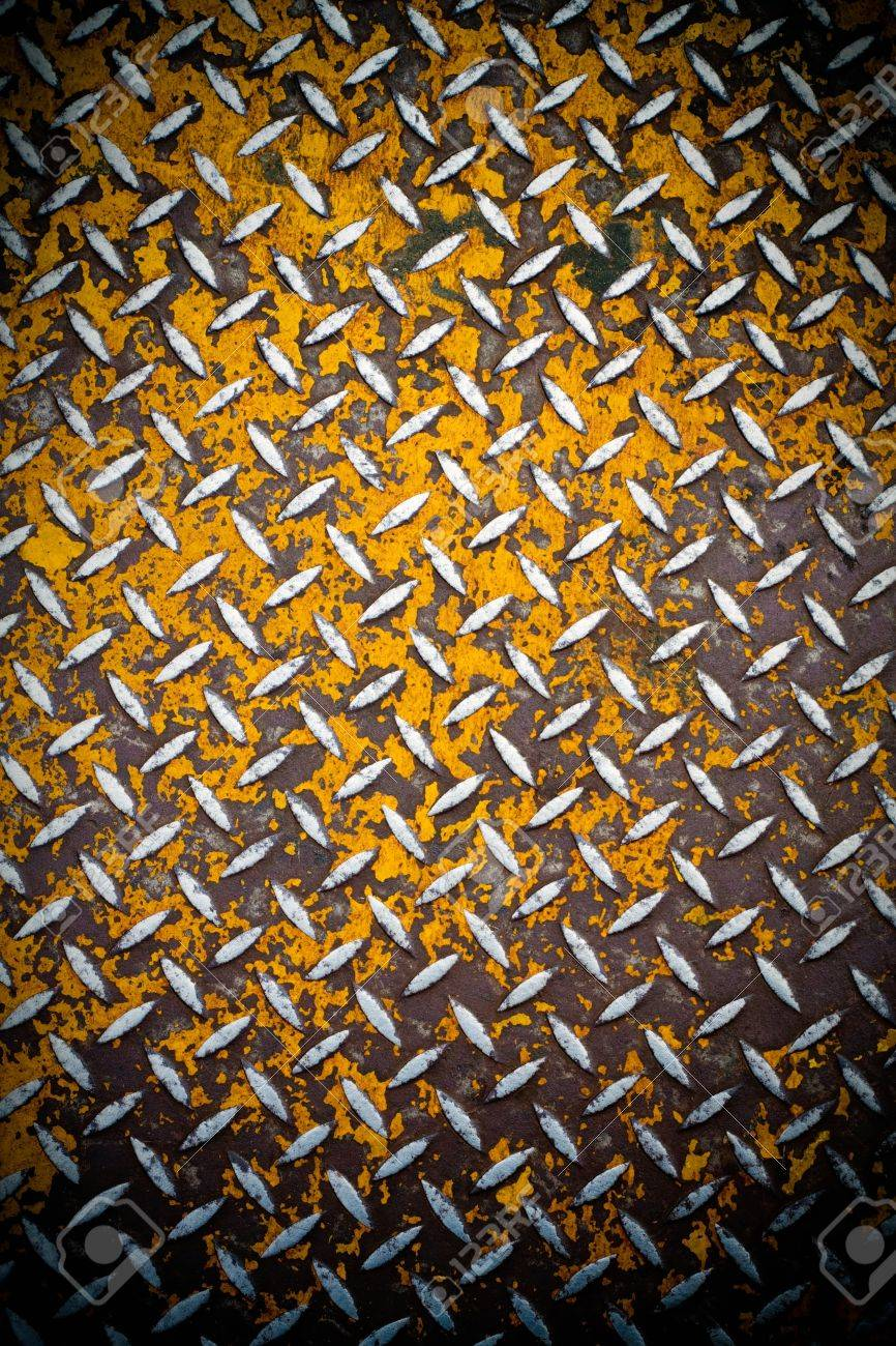 Close up of real diamond plate material with a slight vignette.  Most of the yellow paint is chipped and scratched off. Stock Photo - 9328248