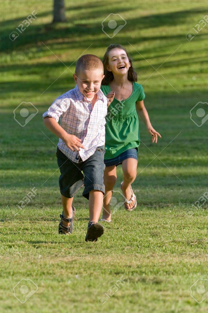 A young brother and sister running through a green grassy field with smiles on their faces. Stock Photo - 11232830