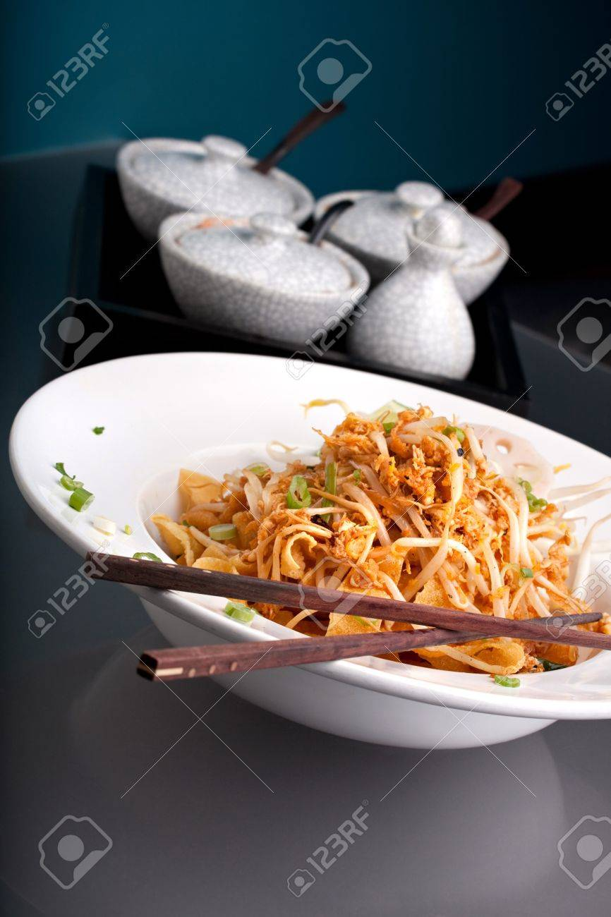 A Thai dish of crisy noodles and bean sprouts in a large white bowl with chop sticks. Stock Photo - 11232855
