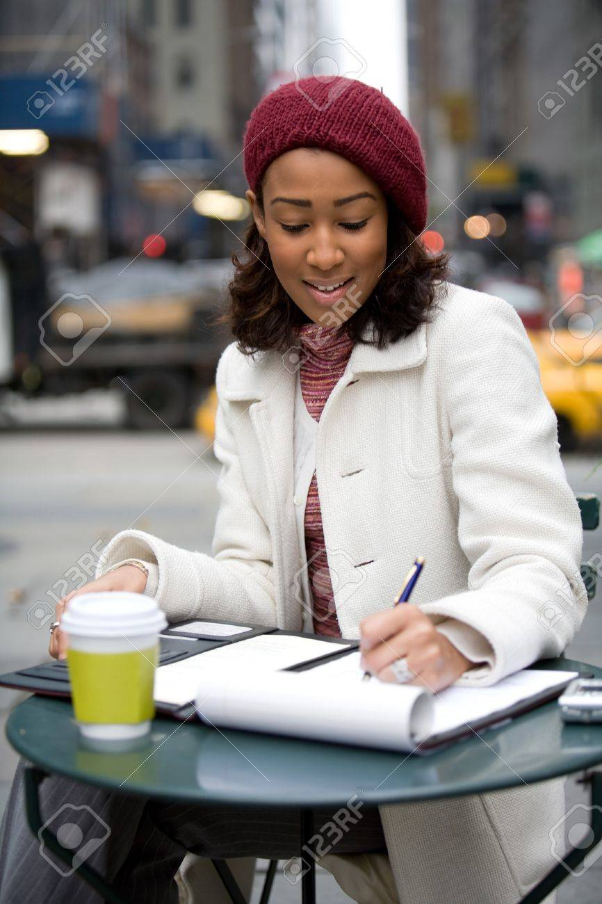 An African American business woman working in the city outdoors writes something down in her notepad. Stock Photo - 16063458