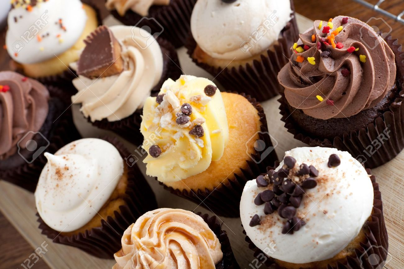 Close up of some decadent gourmet cupcakes frosted with a variety of frosting flavors. Stock Photo - 16270582