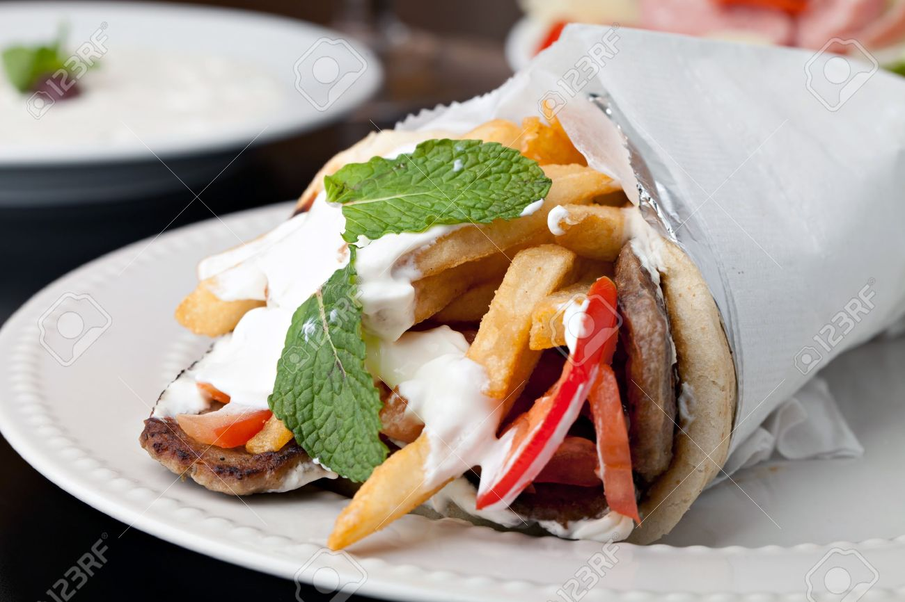 Traditional Gyro sandwich with meat  tzatziki sauce tomato onions and fried potato garnished with mint. Shallow depth of field. Stock Photo - 19508685