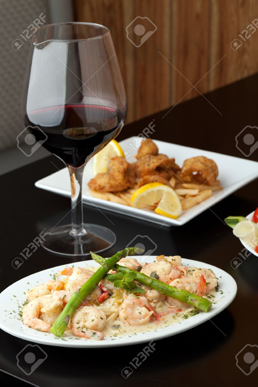 A delicious shrimp scampi pasta dish with red wine and friend shrimp appetizer in the background. Stock Photo - 20209301