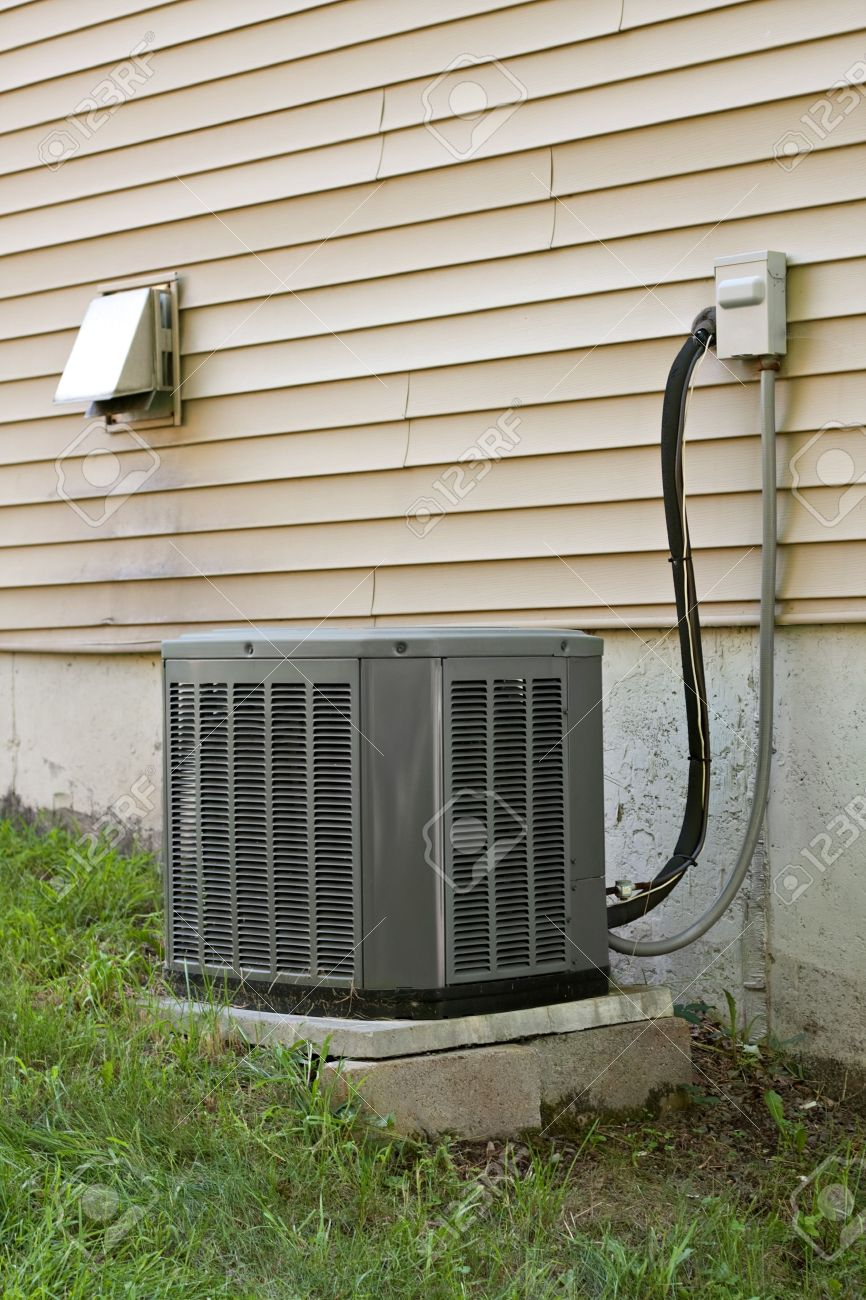 A residential central air conditioning unit sitting outside a home. Stock Photo - 21716776