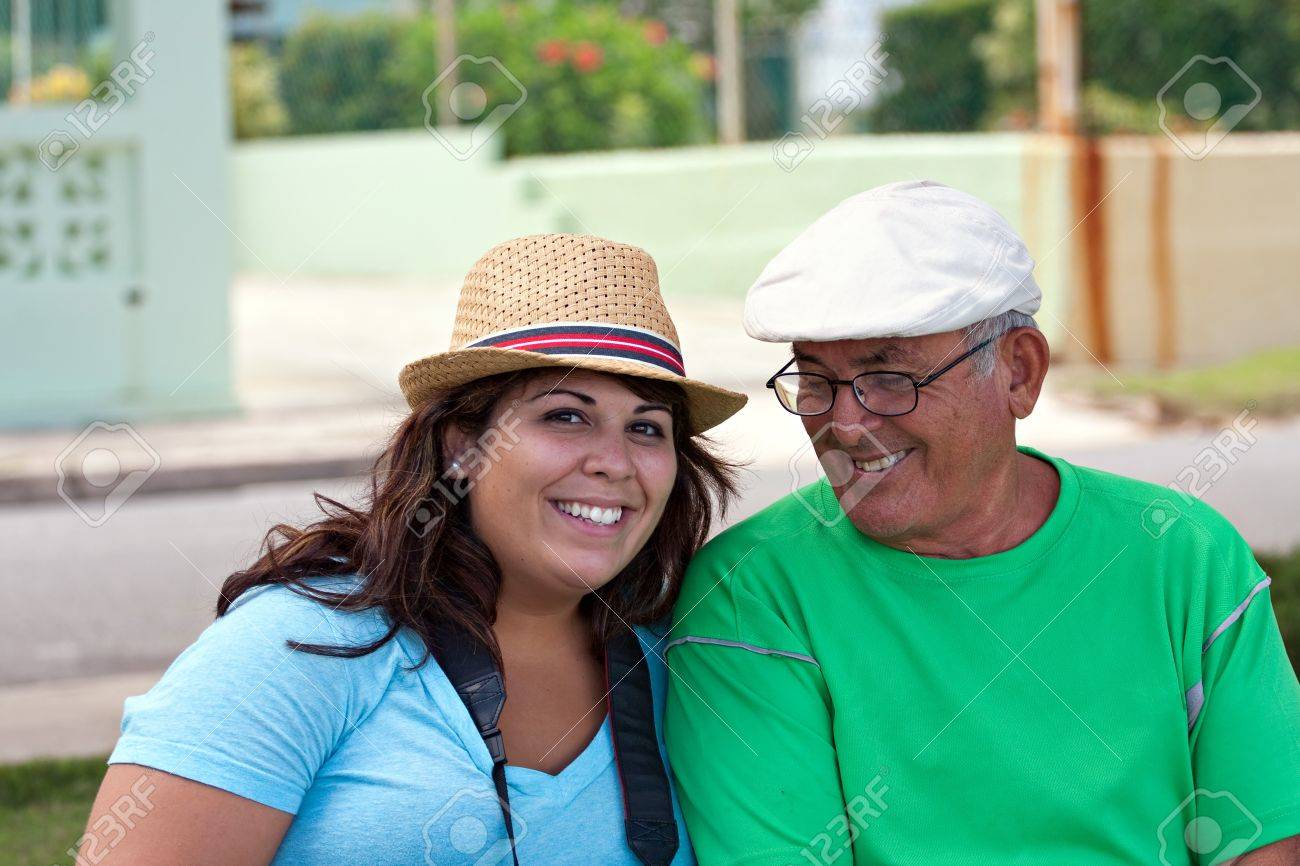 A older Hispanic senior citizen man sits outdoors in a tropical setting with his granddaughter. Stock Photo - 21381694