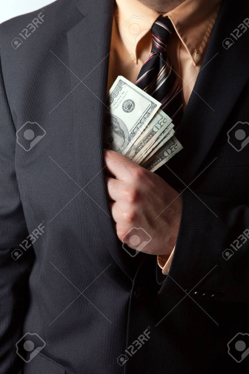 Close up of a business mans hand hiding money in his suit jacket pocket. Stock Photo - 22819670