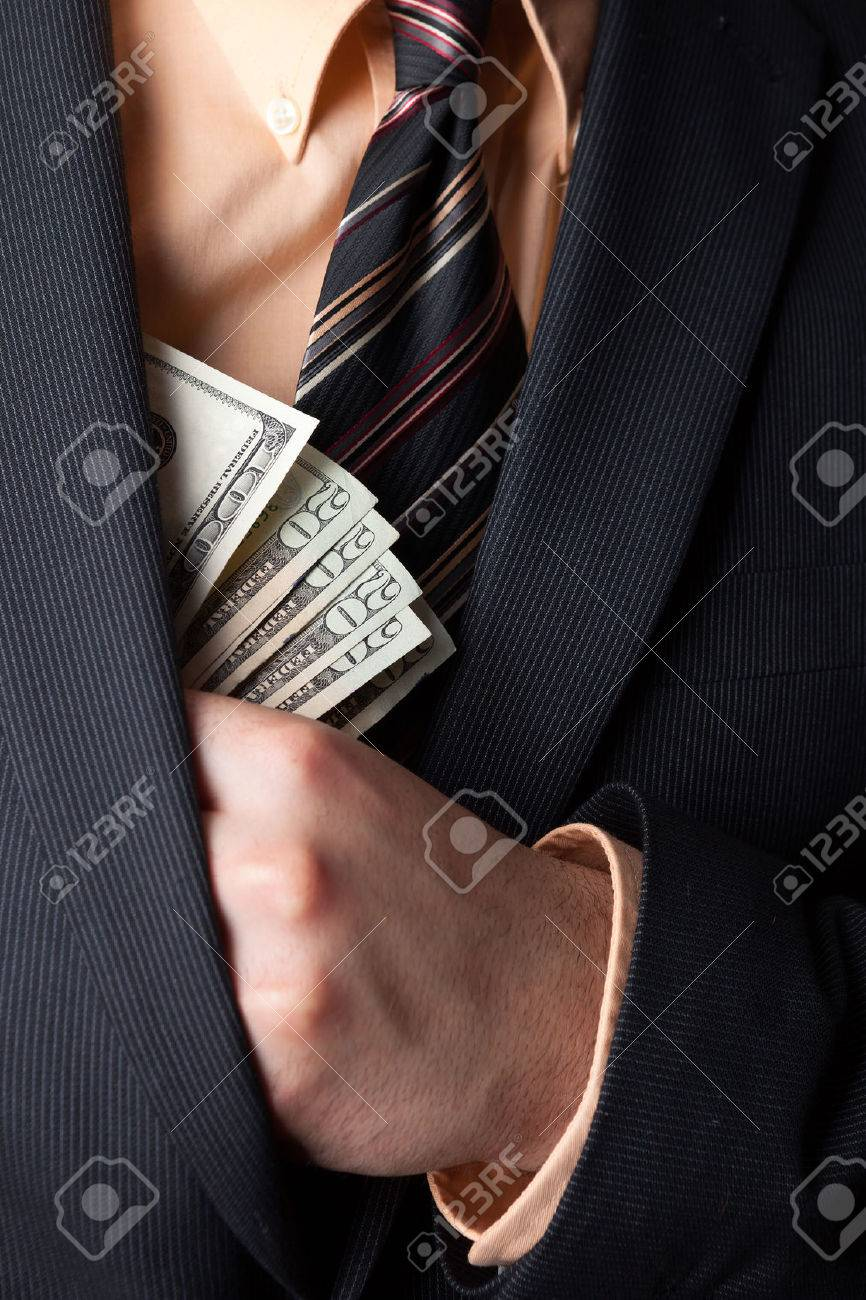 Close up of a business mans hand hiding money in his suit jacket pocket. Stock Photo - 22819671