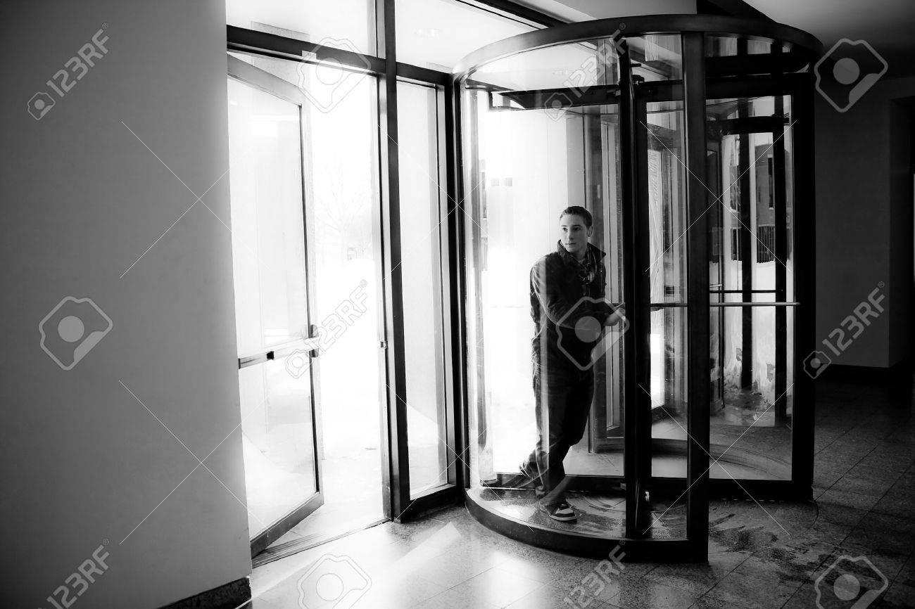 Young man in his twenties walks through a revolving doorway entrance. Black and white. Stock Photo - 23069162
