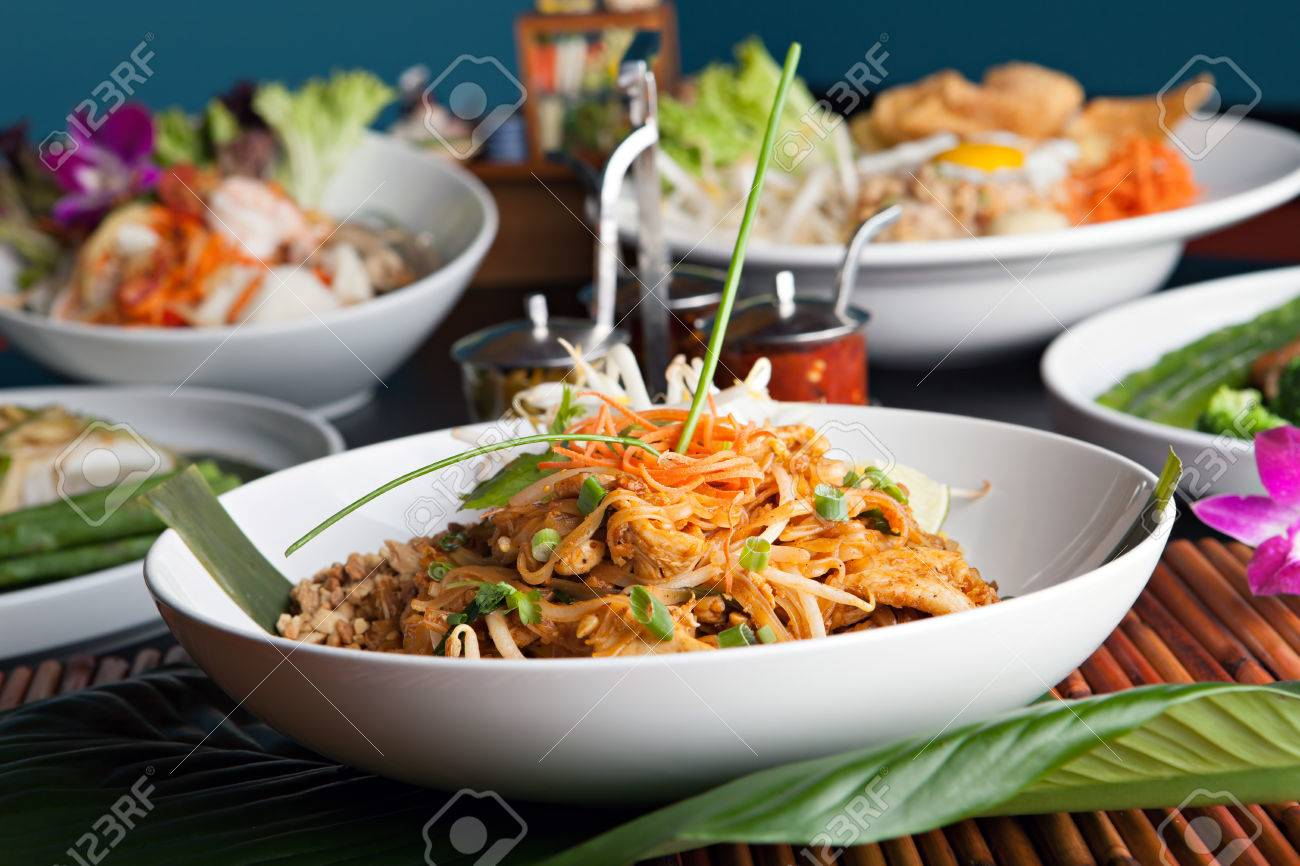 Chicken pad Thai with a variety of other fine Thai food dishes.  Shallow depth of field. Stock Photo - 27741752