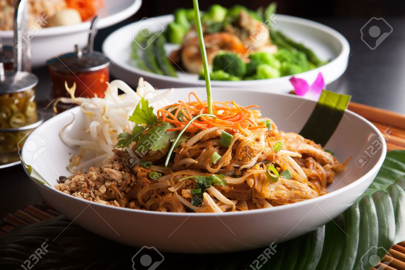 Chicken pad Thai with a variety of other fine Thai food dishes.  Shallow depth of field. Stock Photo - 28681721
