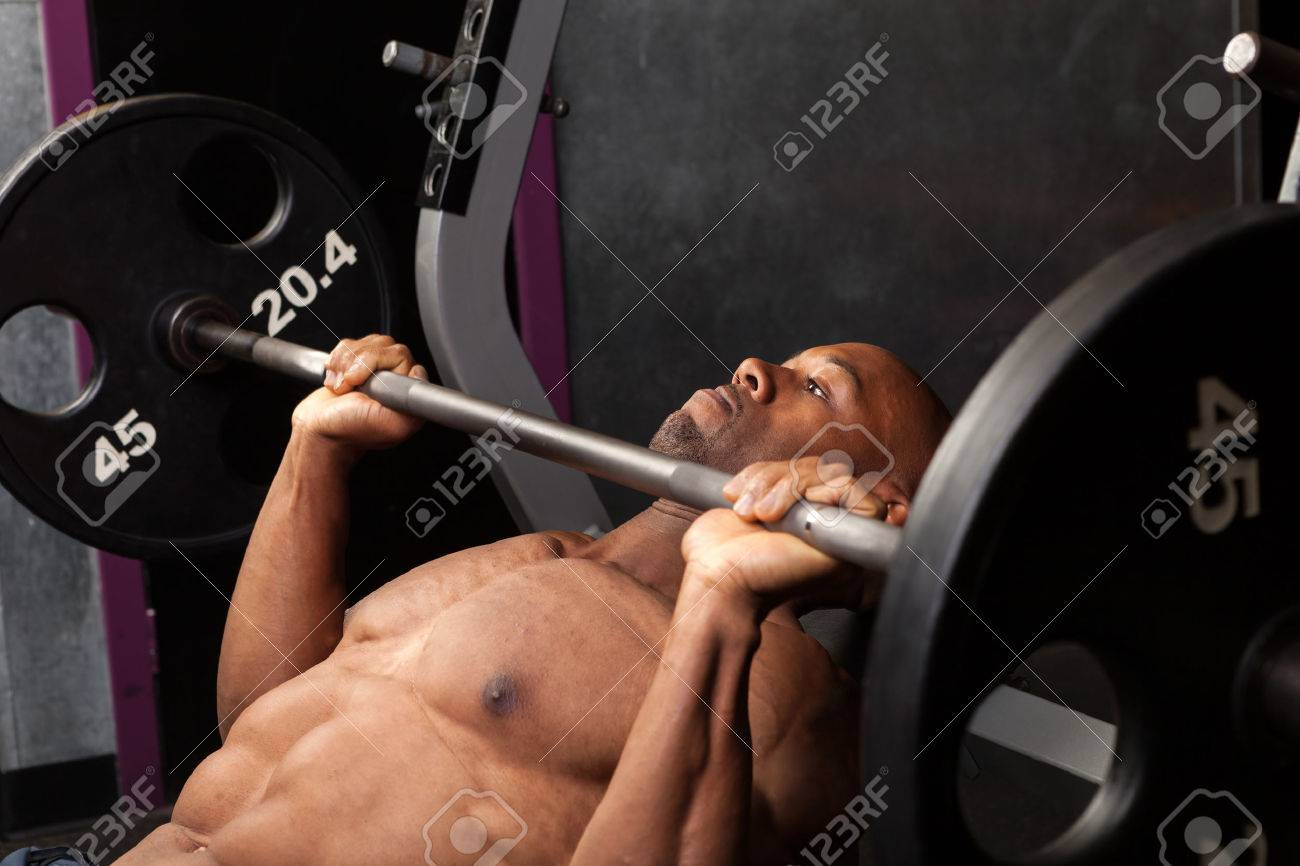 Weight lifter at the bench press lifting a barbell on an incline bench. Stock Photo - 33587035
