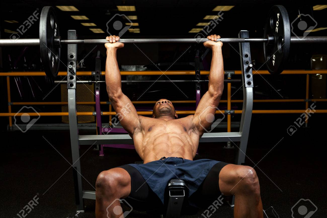 Weight lifter at the bench press lifting a barbell on an incline bench. Stock Photo - 35691527