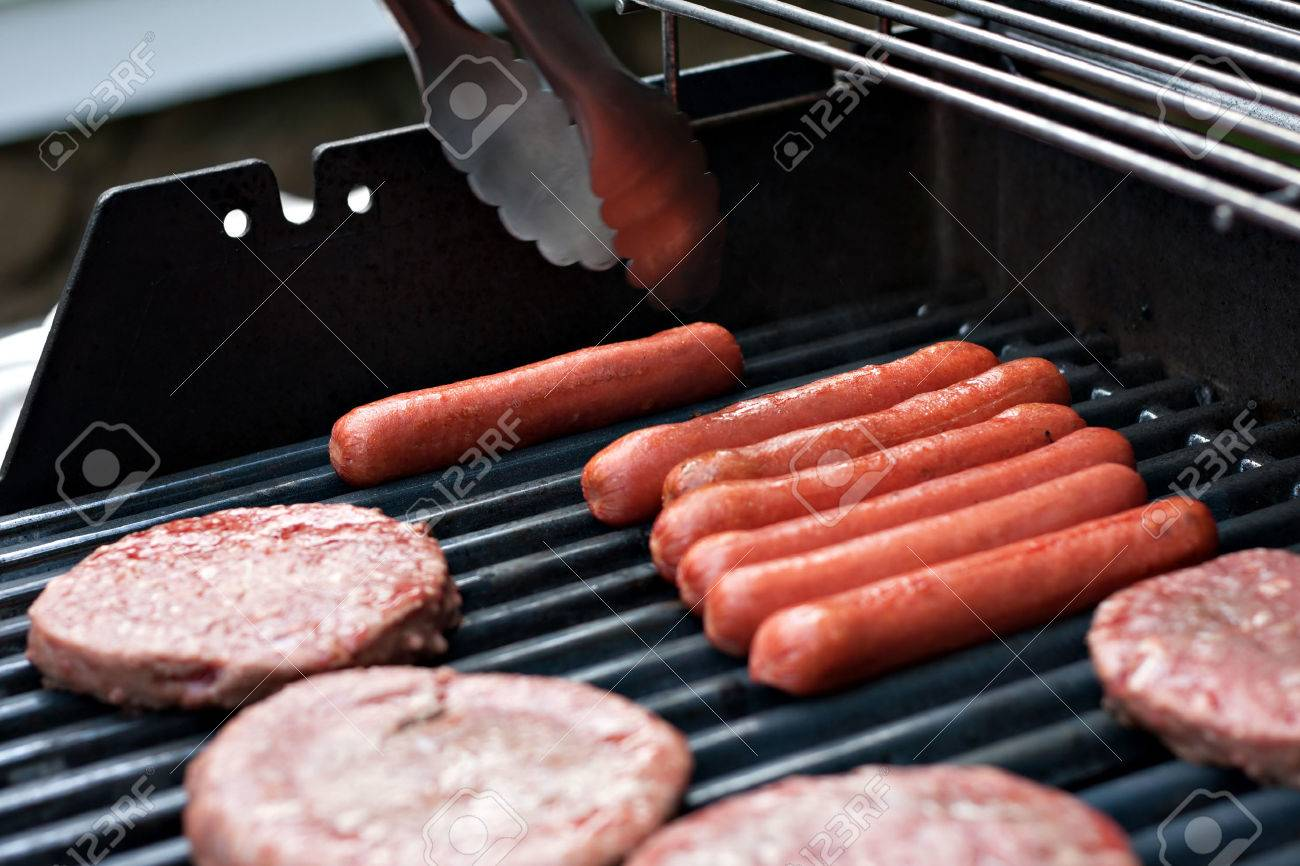 A closeup of some fresh and juicy hamburgers cooking on the grill. Stock Photo - 36583034