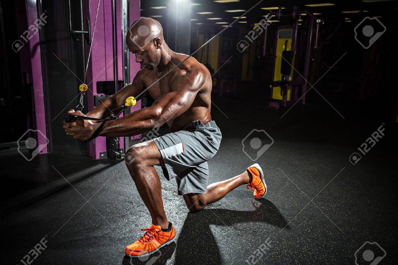 Muscular body builder working out  at the gym doing chest fly exercises on the cable wire machine. Stock Photo - 40877993