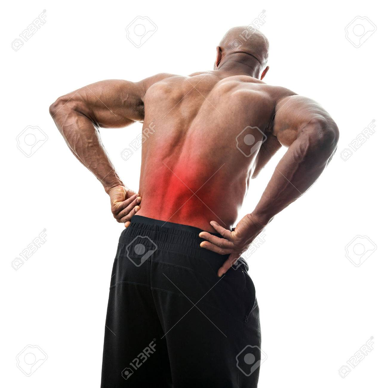 Fit man or athlete reaching for his lower back in pain with the painful area highlighted in red. Stock Photo - 43825899
