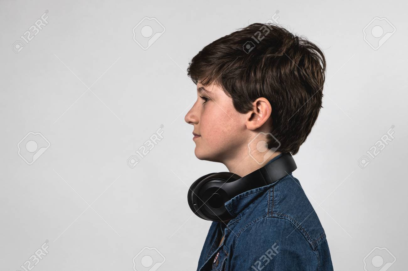profile of teenage boy listening to music with headphone not stock