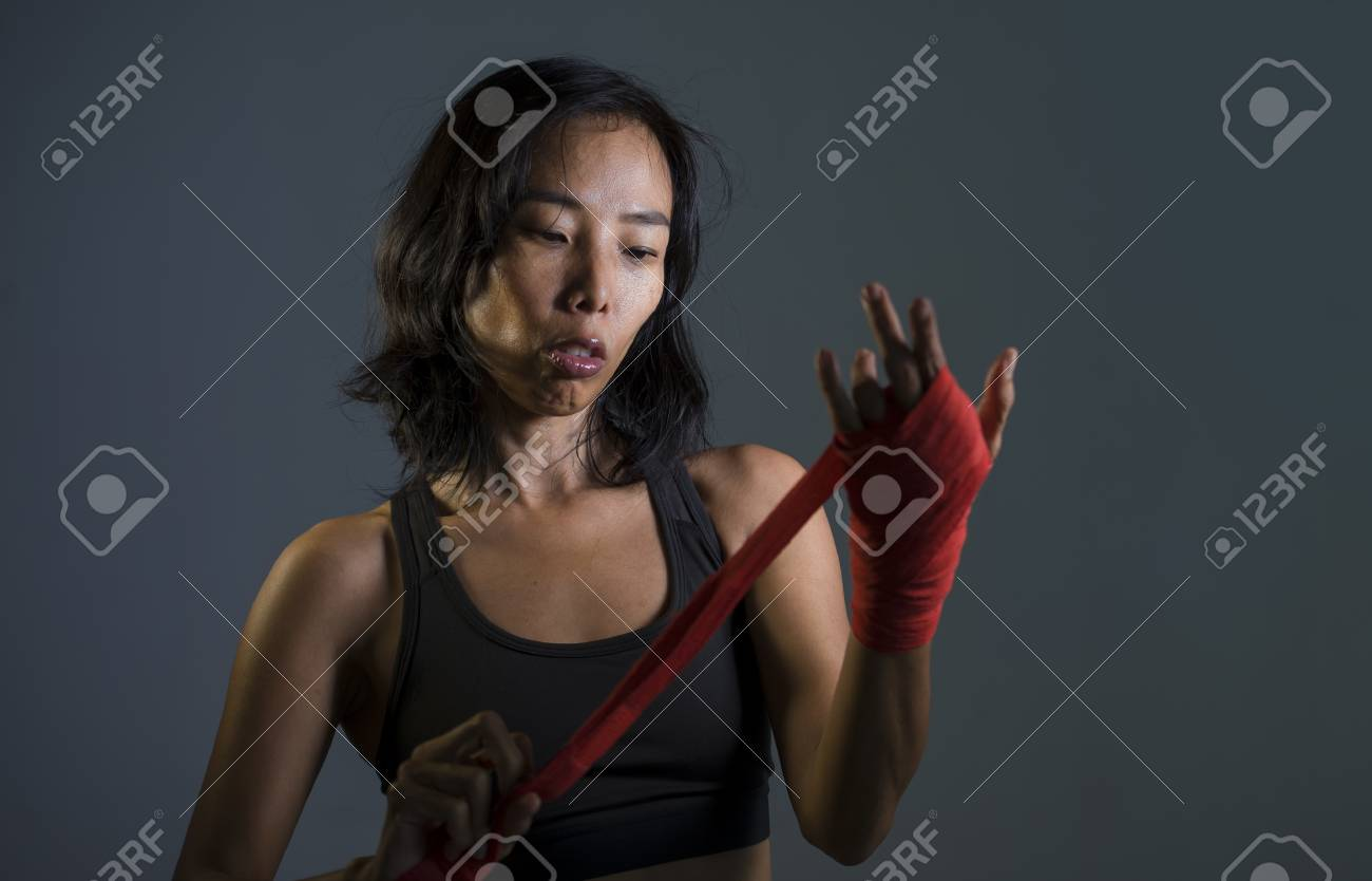 portrait of sporty and fit fighter Asian Chinese woman using