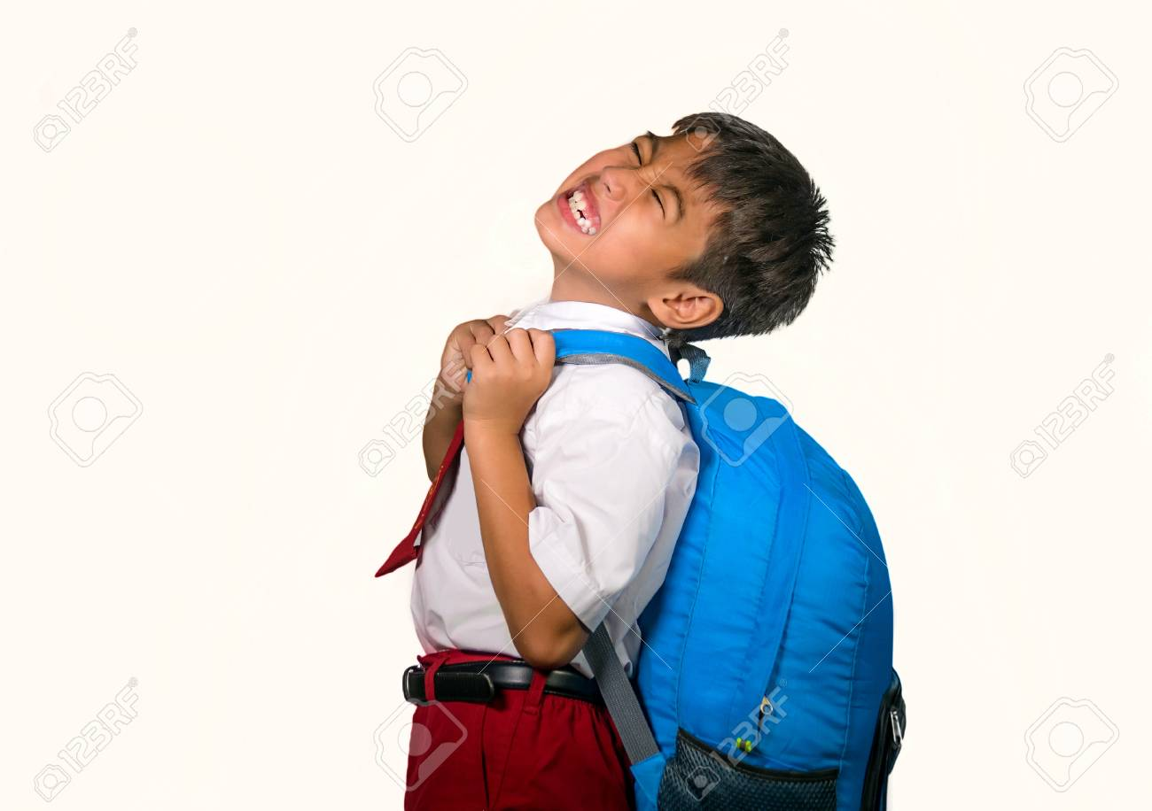 7 or 8 years old sweet kid in uniform carrying bag full of books feeling  upset 6ad1d7090aac