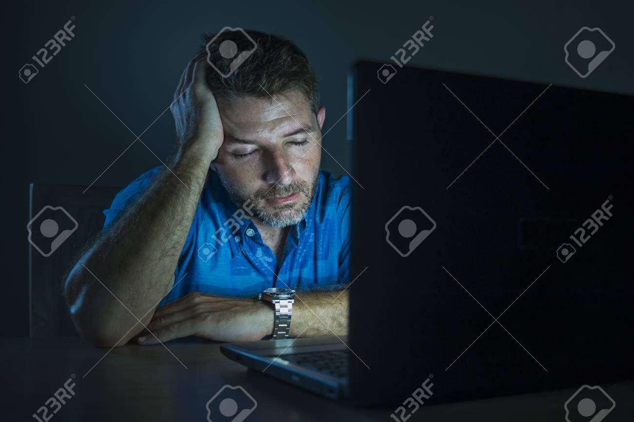 young attractive and tired unshaven man working late night on laptop computer in the dark feeling frustrated and exhausted in freelance entrepreneur business concept - 113502893