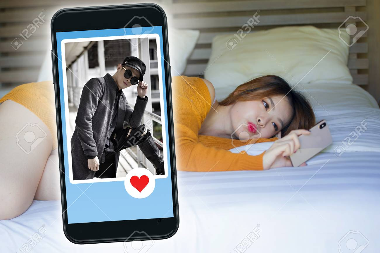 young beautiful and happy Korean woman in bed using mobile phone