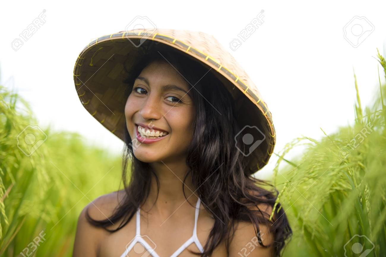 young happy and beautiful latin woman playing with traditional Asian farmer hat smiling having fun posing isolated on green rice field in Asia tourist trip and Summer holidays travel - 121045974