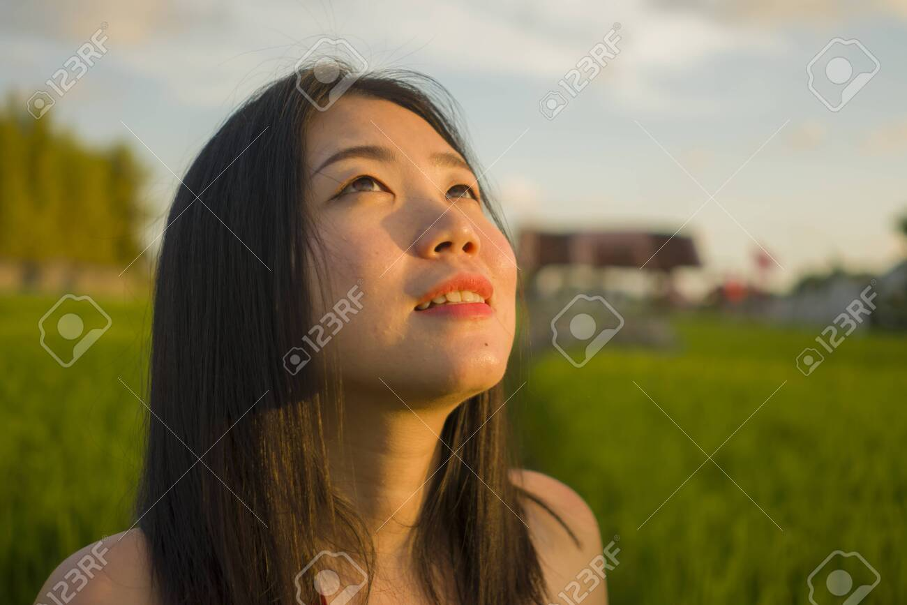 young happy and beautiful Asian woman enjoying nature at rice field. sweet Chinese girl in Summer dress at green field exploring countryside during holiday travel in wanderlust and tourism - 131985902