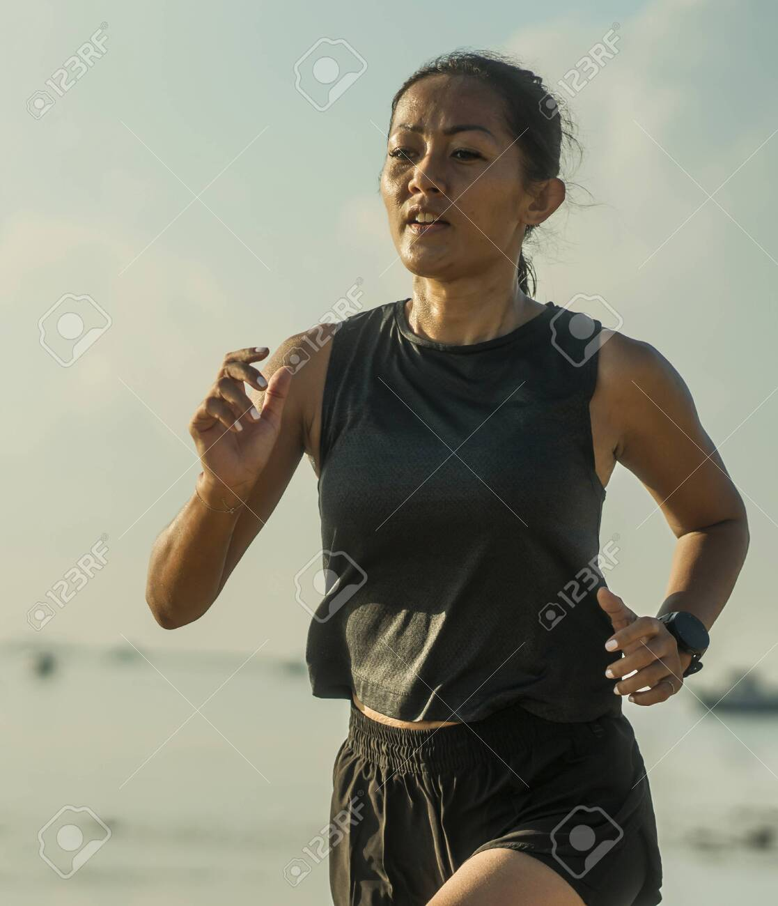 outdoors fitness portrait of young attractive and athletic Asian Indonesian woman in her 40s running on the beach doing intervals workout in athlete training concept and healthy lifestyle - 140318296