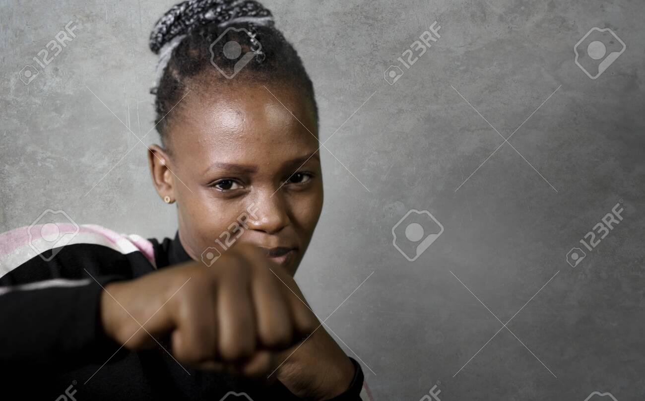 isolated portrait of young cool and confident black afro woman in fighting stance looking defiant rising her fist throwing punch in badass attitude isolated on grunge background - 148527029