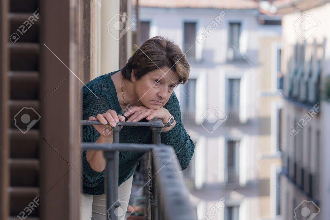 dramatic lifestyle portrait of mature woman on her 70s depressed and sad at home balcony feeling desperate suffering anxiety problem in senior female depression concept - 158052389