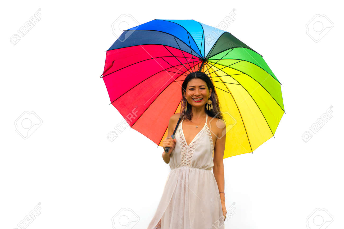 attractive and happy Asian woman holding rainbow colorful umbrella or parasol smiling playful isolated on white background in beauty and freedom concept - 168484804